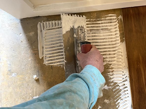 With a notched trowel, spread the GreenGrip hardwood adhesive over the foundation where you would like to lay the new flooring.