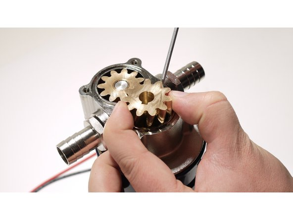 Using the flat head screwdriver apply some force between two teeth and try to lift the gear. Use the other hand or a plier (usually you don't need it) to take the first gear away.