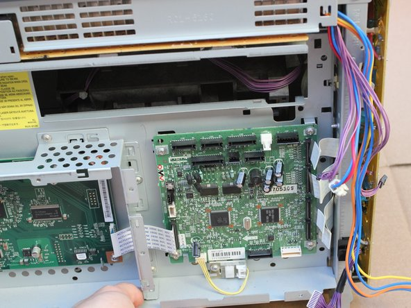 Remove the circuit board assembly from the printer, being cautious of the wires and cables,