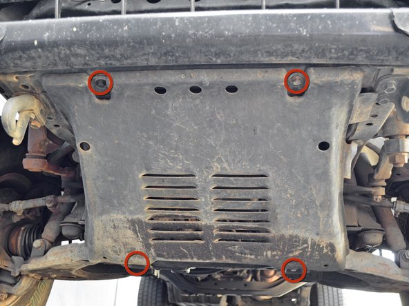 Locate the four 12 mm hex bolts holding the skid plate to the chassis.