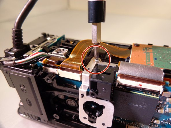 Remove one silver 5 mm screw from the front right side of the camera where the orange motherboard card is.