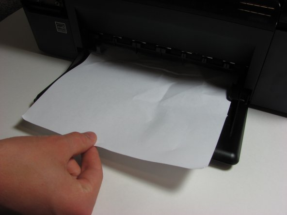 Use your hand to gently remove the jammed paper. Pull the paper until it is completely out.