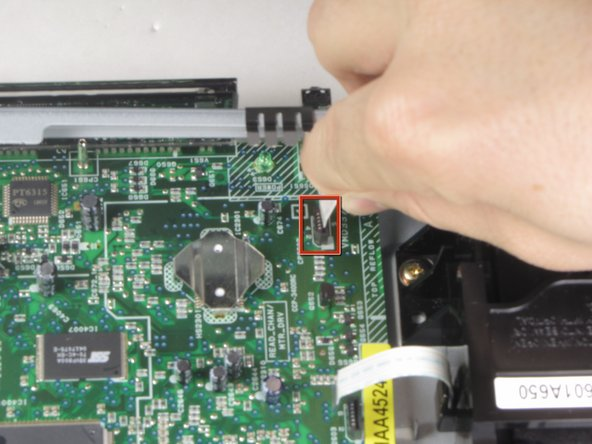 Remove the third of three ribbon cables on left hand side of disc drive by pulling vertically.