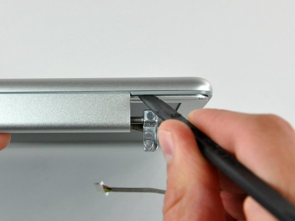 Insert the flat end of a spudger between the front display bezel and the plastic rim attached to the rear bezel near the lower left corner of the display.