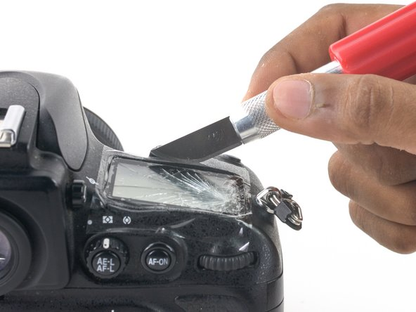 Insert the curved razor blade between the long edge of the LCD and the body of the D800.