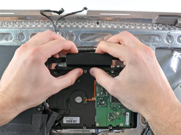 Compress the plastic hard drive retainer by pushing it toward the bottom edge of the iMac.