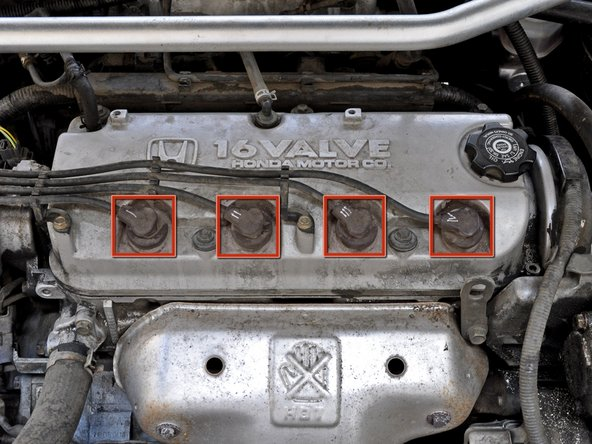 Begin by locating the four spark plug connectors near the front of the valve cover of your engine.