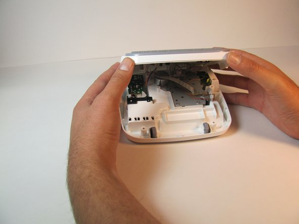 Close the back cover and then flip the device over and separate the top half from the bottom half as shown.