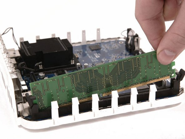 Grasp the RAM chip at the end opposite of the back ports, and pull directly up.