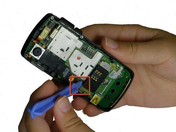 Use a plastic opening tool to gently lift up the SIM card reader, located above the rubber antenna casing. You should hear a click as it releases.