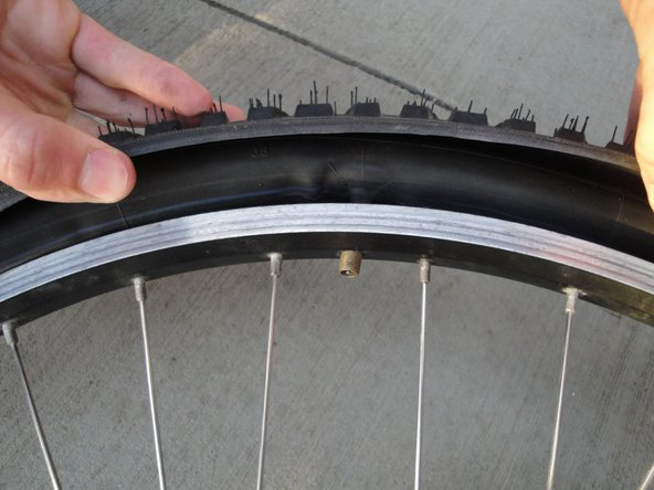 Remove the tube by pushing the valve through the hole in the rim and pulling out completely.