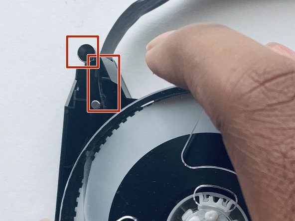Place the left reel into the replacement shell, making sure the tape goes in-between metal circular piece and  the plastic triangular piece pictured.