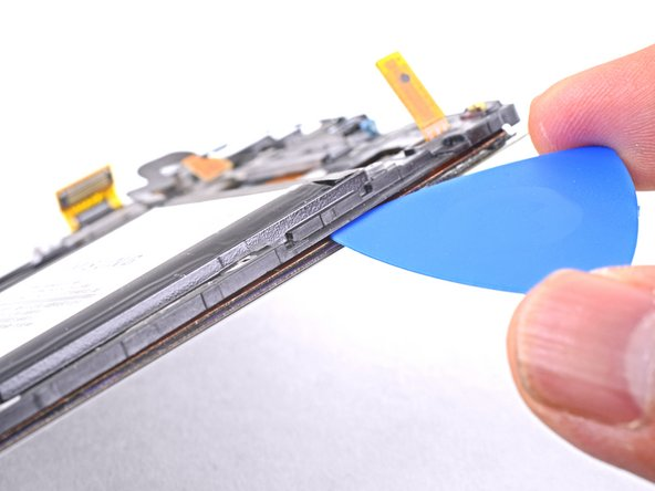 Insert an opening pick between the plastic frame and the display assembly on the same edge you just heated.