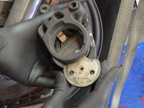 Being careful to not let any loose parts fall out of the brake assembly, remove the stationary brake pad from the front brake assembly.