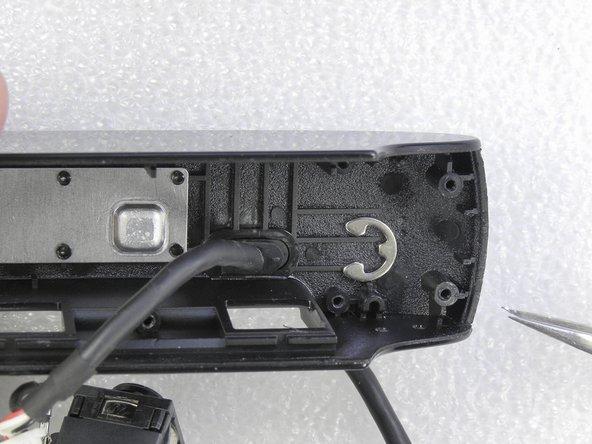 Solte o clips que prende o suporte do cabo. Puxe esse suporte do cabo, para fora da camera.