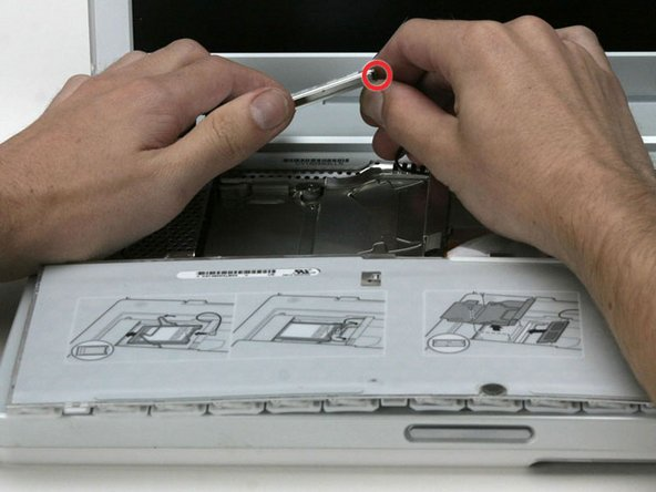 Hold the Airport card in one hand and use your other hand to remove the antenna cable.
