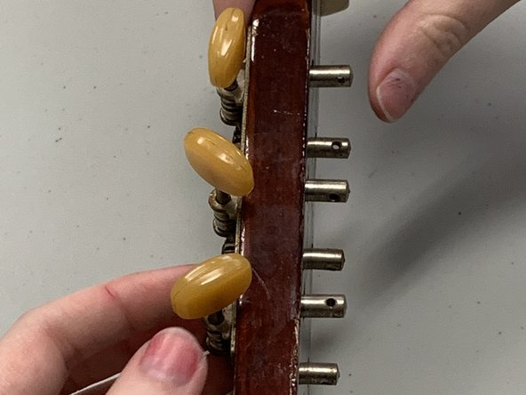 Remove the old tuning keys by sliding them out of the holes.