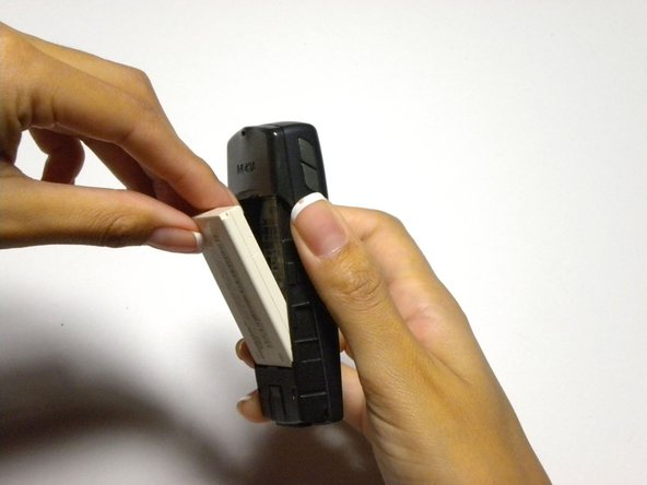 Lift the battery out of the phone by pushing down from the top and pulling out