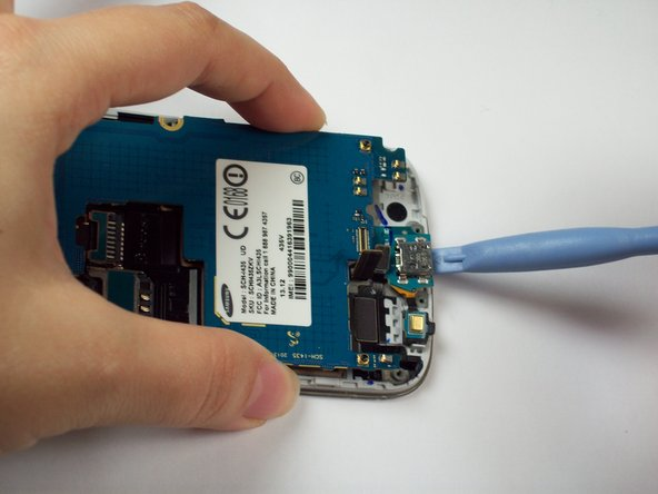 Gently pry underneath the charging port using the plastic opening tool to separate it from the double sided tape below.