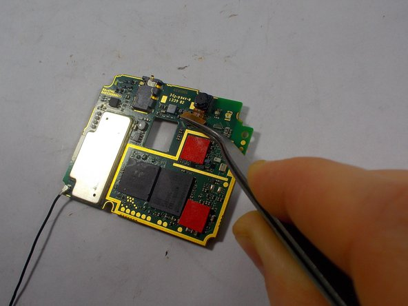 Use a pair of tweezers to disconnect and remove the front facing camera from the motherboard.