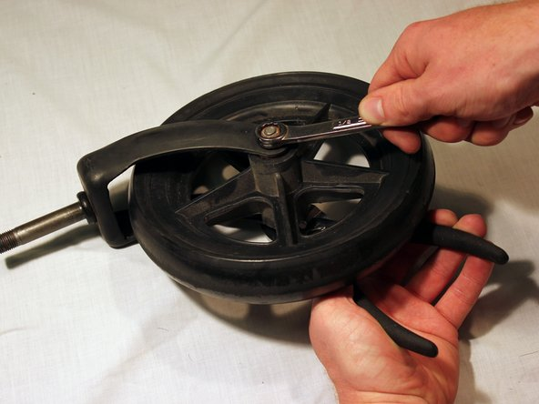 Hold the bolt that connects the wheel to the fork with pliers.