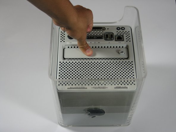 Release the back handle of the PowerMac. Slowly pull out the cube by holding the end of the handle. Watch for any parts that may become entangled with the outer case.