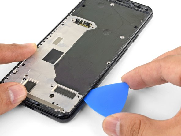 Slide the opening pick along the left and right edges of the phone to release the midframe clips.