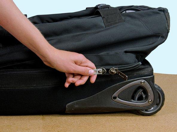 Das Rollengepäck mit der Vorderseite nach oben auf einen Tisch legen.
