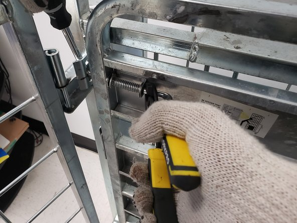 At the same time, wedge the screwdriver behind the locking mechanism.