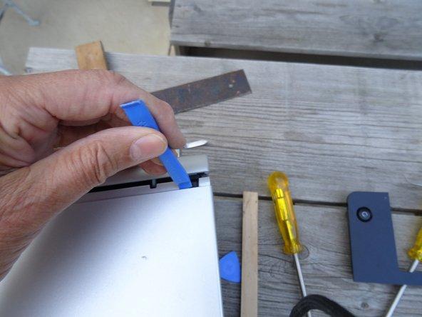 Schiebe das Seitenteil kräftig nach hinten. Es klemmt vielleicht ein bisschen und du musst mit einem Hebelwerkzeug aus Kunststoff nachhelfen.