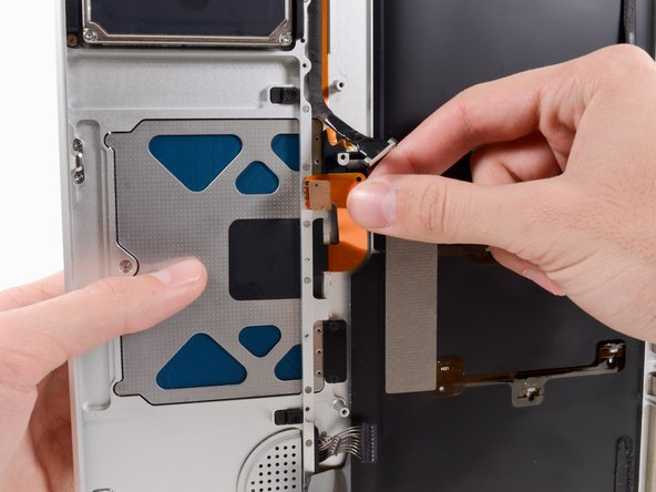While holding the trackpad in place with your left hand, fold the top of the trackpad ribbon cable down with your right hand so that it fits through its slot in the upper case.