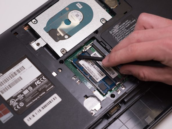 Gently push the metal hinges outwards from the RAM.