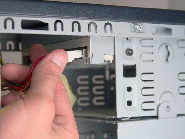 Remove the IDE data cable and the power cable from the optical drive by pulling away from the drive.