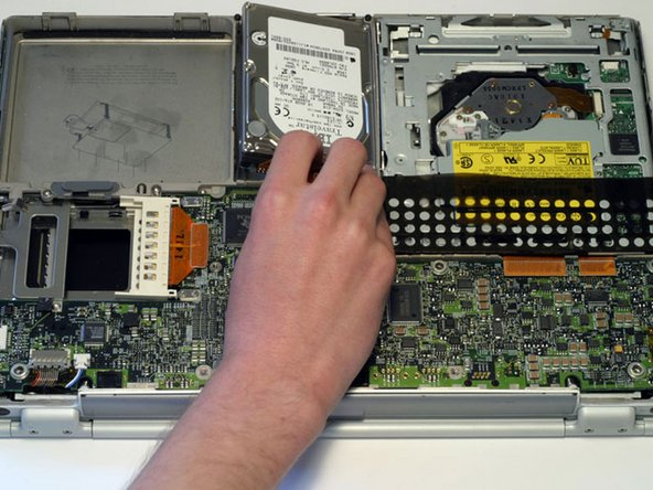Remove the hard drive by gently grasping the orange ribbon cable and lifting the left edge up and out of the computer.