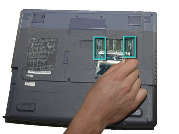 Release the plastic switches on each side of the stick of RAM.