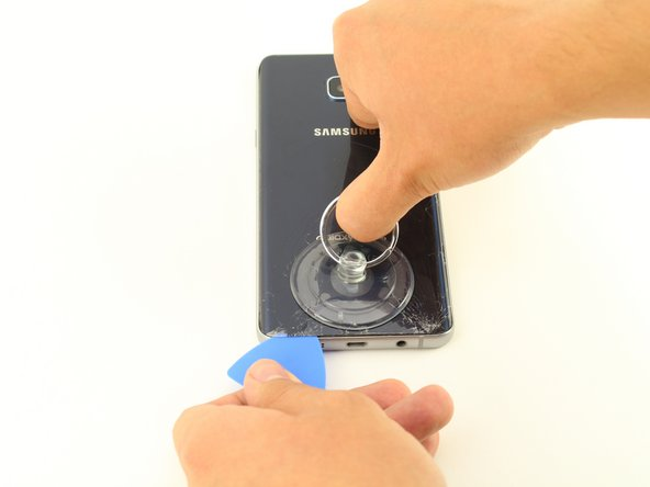 Once the device is heated, place a suction cup near the bottom of the back of the device Make sure it is placed on the flat part of the glass