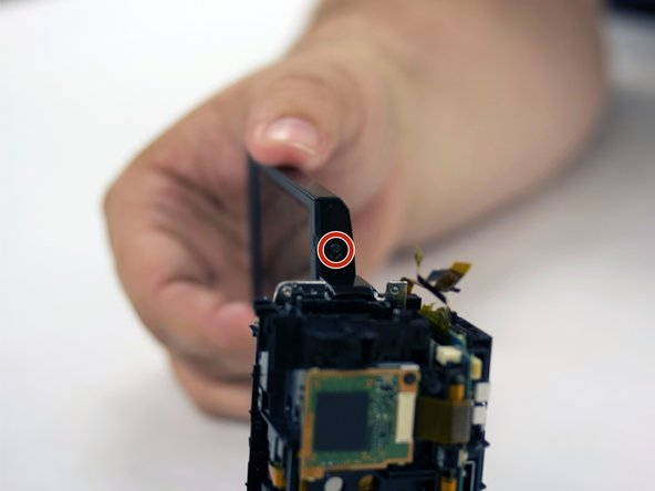 Rotate the LCD screen on its hinge +/- 90 degrees relative to the camera to expose the screws on the side of the LCD panel.