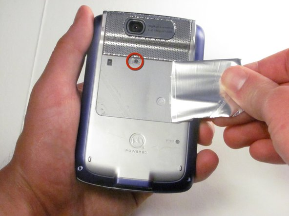 Peel back the adhesive label below the camera on the rear to reveal a hidden screw, circled in the picture to the left.