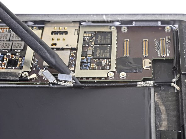 Use the point of a spudger to pry up and loosen the adhesive holding the two disconnected antenna cables in place.