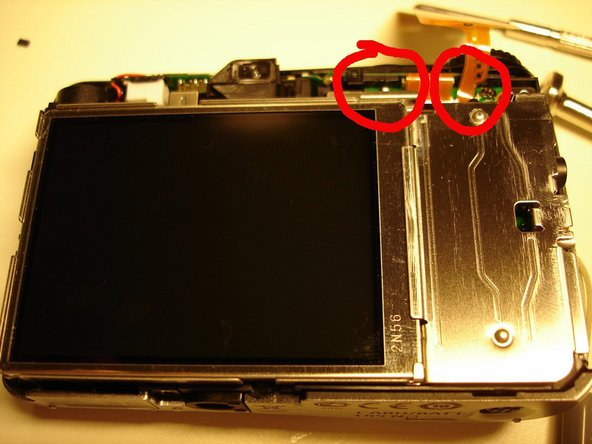 First you need to remove the back cover of the camera, so that you can access the motherboard. Here is how it looks like with the backcover removed (4 scew removed for a powershot A1200). At the top, you can see the main pins connecting the battery contact to the motheboard, but it is difficult to access them.