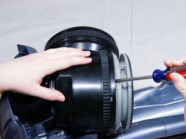 Insert flat head screwdriver between gray motor housing and black motor.