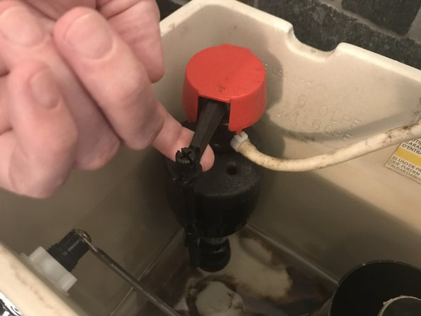 Gently lift the float up, ending the flow of water. This will prevent the toilet tank from refilling.