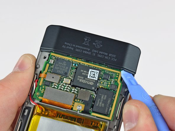 Insert a small Zune opening tool into the gap between the logic board and one side of the black plastic lower rear panel.
