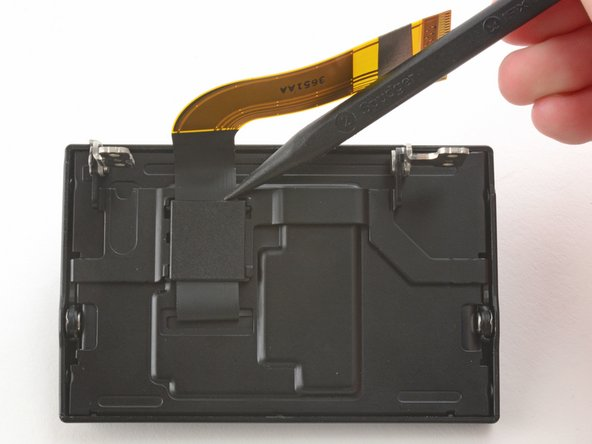 Use the pointed end of a spudger to remove the ribbon cover on the back of the LCD.