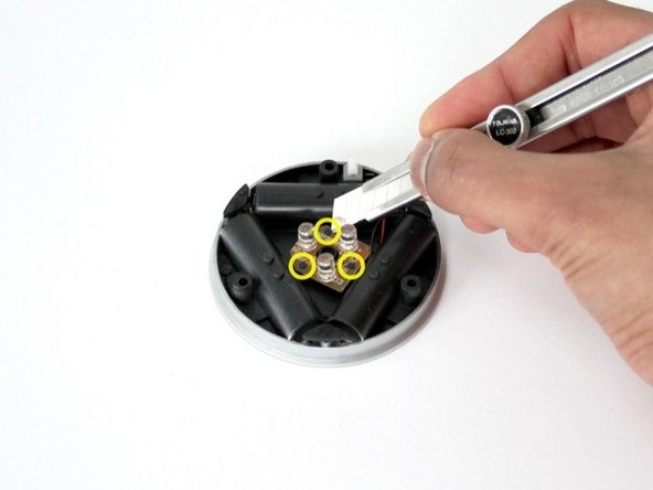 Using the craft knife, slice off the black plastic extrusions at the indicated positions. These tabs secure the circuit board to the main assembly.