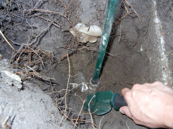 Dig around the pipe fitting with a trowel to provide clear access.