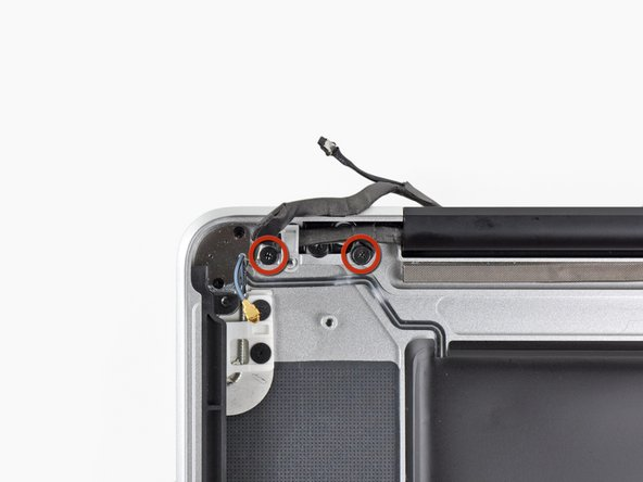 Remove the two 7.1 mm Phillips screws securing the camera cable retainer to the upper case.