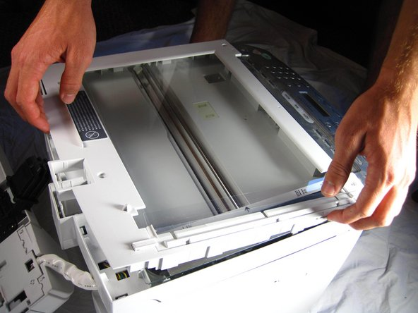 Gently, pry off the top plate, starting from the back of the printer.