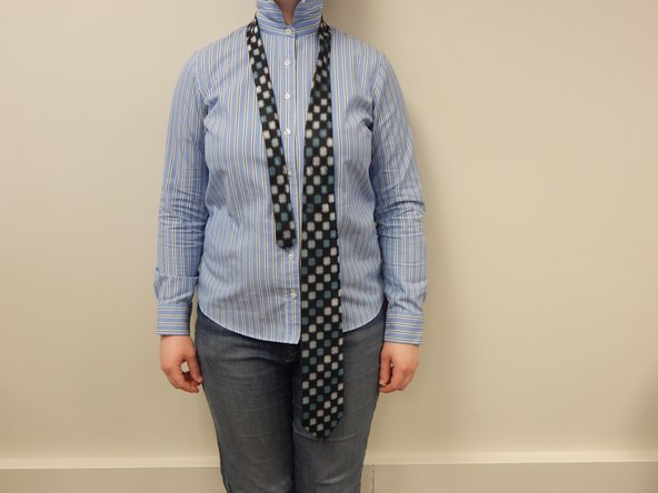 Wrap the tie around the back of your neck with the narrow end on the left side of your body and the wide end on the right side.