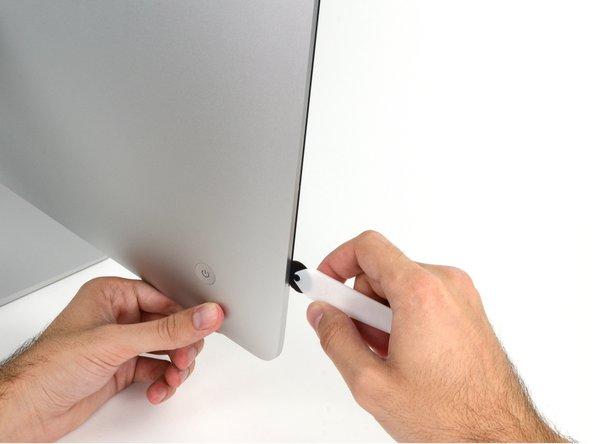 Iniziare sulla parte sinistra del display, accanto al pulsante di alimentazione, inserire l'attrezzo per l'apertura dell'iMac nello spazio fra il pannello di vetro e il case posteriore.